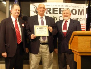 "Conference Event Coordinator Richard Buck (left) and Richard Conn (right) present ""Honorary Membership"" Certificate to Christopher Carmouche after his remarks at the February Freedom Leadership Conference sponsored by Grasstops USA, where he is President."