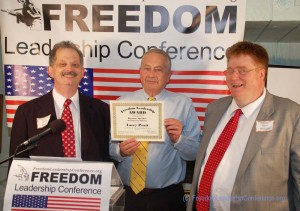 "Larry Pratt was awarded a ""Freedom Leadership Award"" for his efforts in defense of freedom by the conference leadership at the end of his presentation, along with an ""Honorary Conference Membership"" (both presented to all conference keynote speakers), Richard Buck (left), Ronald Wilcox (right)."